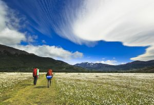hikers going in patagonia mountains with beautiful clouds